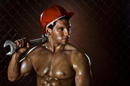 müdigkeit: closeup Portr�t der Sch�nheit muskul�se Arbeiter, rot Schutzhelm mit gro�en Schraubenschl�ssel in der Hand, schmutzig und verschwitzt