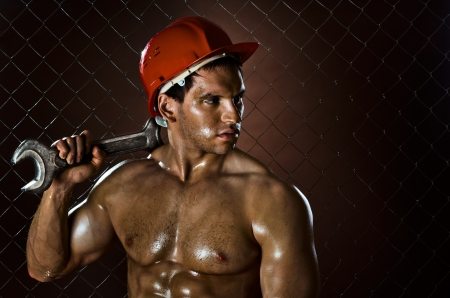 closeup portrait  the beauty muscular workman, in red safety helmet  with big  adjustable wrench  in hand, sordid and sweaty