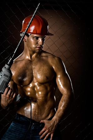 the beauty muscular worker driller man ,  hold  big perforator in hand,   photo