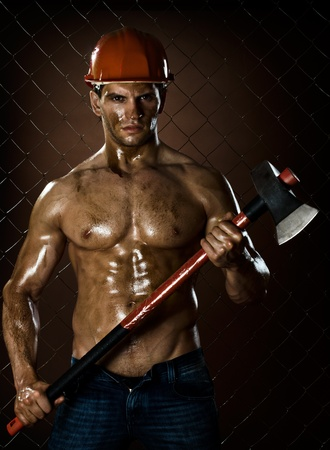dirty man: the beauty muscular worker  chopper  man, in  safety helmet  with big  heavy ax  in hands,  on netting fence background
