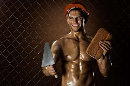 rigger:  the beautiful  muscular worker  man, in  safety helmet  with trowel and brick  in hands and smile, on netting fence background Stock Photo