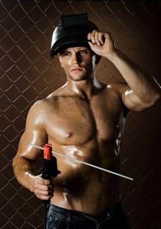 cansancio: cansancio trabajador musculoso hombre soldador, soldadura de arco de soldadura, sobre la compensaci�n fondo valla Foto de archivo