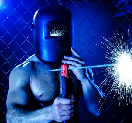 the beauty muscular worker welder  man, weld  electric arc-weld, on netting fence background Stock Photo - 17221369