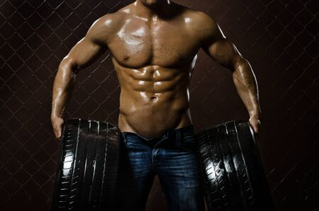 muscularity: the very muscular handsome sexy guy with rubber-tire,  on  netting  steel fence background Stock Photo