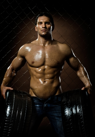 brutal: the very muscular handsome sexy guy with rubber-tire,  on  netting  steel fence background Stock Photo
