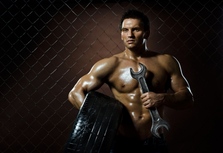 brawny: the very muscular workman with rubber-tire and big wrench,  on  netting  steel fence background