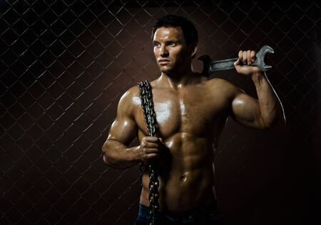 miry: the beauty muscular worker  man,  with big wrench and  chain in hands, on netting fence background