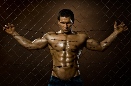 the very muscular handsome felon guy , misery  out of netting   steel fence with  barbed wire Stock Photo - 17221570