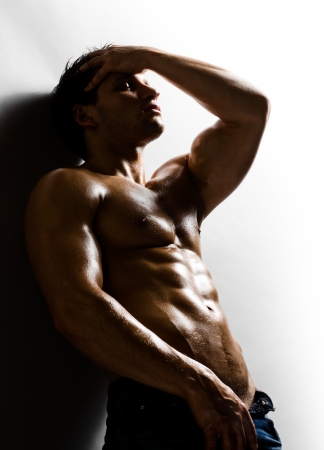 the very muscular handsome sexy guy on   grey wall  background photo