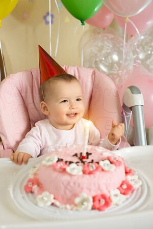 solemnize: one-year-old little girl solemnize birthday, happy laughter  Stock Photo