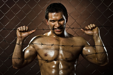 the very muscular handsome felon guy ,  out of netting   steel fence with  barbed wire Stock Photo - 17221578