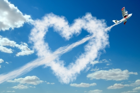 twin-engine hydroplane flight in sky and draw white heart of  clouds , St. Valentines Day  concept