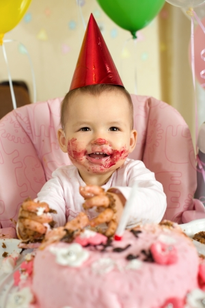 solemnize: one-year-old little girl with  dirty-faced solemnize birthday, happy laughter