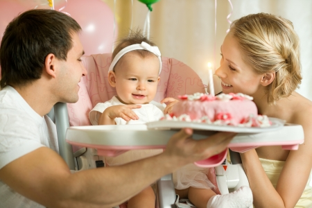 one-year-old little girl with daddy and mammy solemnize birthday, happy laughter  Stock Photo - 17221588