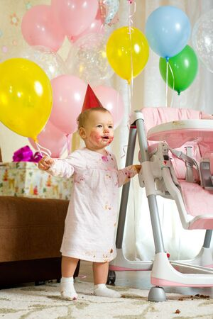 solemnize: one-year-old little girl solemnize birthday with dirty-faced, stand  Stock Photo