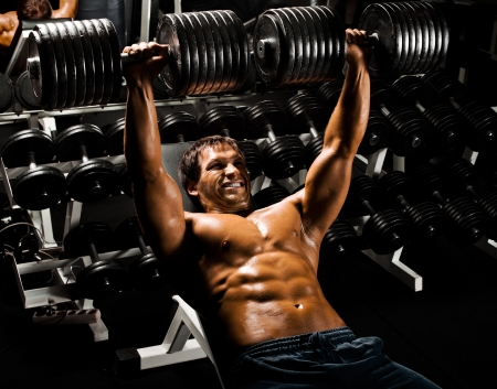 very power athletic guy ,  execute exercise press with  dumbbells, in sport hall Stock Photo - 17646420