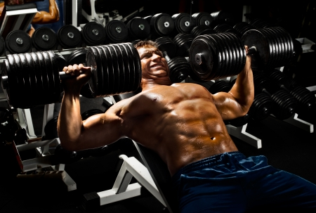 very power athletic guy ,  execute exercise press with  dumbbells, in sport hall Stock Photo - 17646421