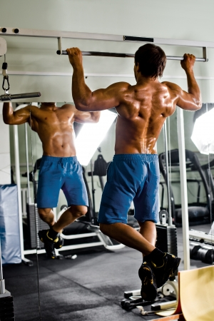very power athletic guy ,  execute exercise tightening  on horizontal bar, in  sport-hall, glamour light Stock Photo