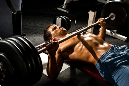 very power athletic guy ,  execute exercise press with weight, in sport hall Stock Photo - 17646417