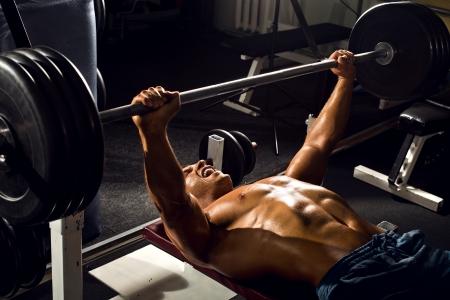 culturista: muy chico potencia atlética, ejecutar prensa ejercicio con peso, en pasillo de deporte Foto de archivo