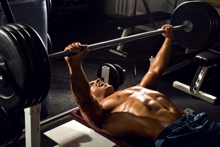 very power athletic guy ,  execute exercise press with weight, in sport hall