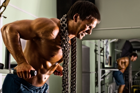 very power athletic guy ,  execute exercise on parallel bars, in sport hall Stock Photo - 17767465