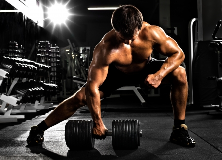 dumbbells: very power athletic guy ,  execute  traction with  dumbbells, exercise on broadest muscle of back, in sport hall