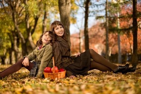 딸과 함께 행복 한 어머니는 단풍 잎에 앉아 미소