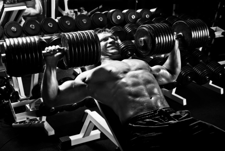 hardy: very power athletic guy ,  execute exercise press with  dumbbells, in sport hall,  black-and-white photo