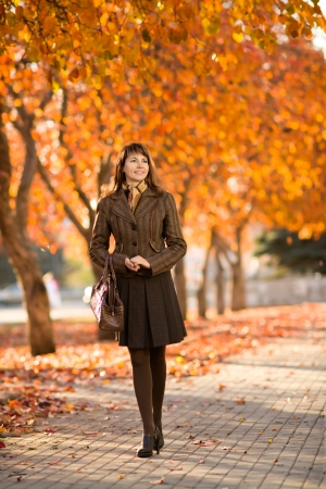 The happiness mature beautiful woman, walking outdoor in park, autumnal day Stock Photo - 18007798