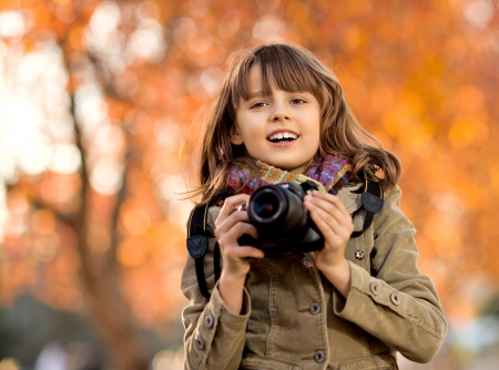 horizontal photo, happy beautiful little girl with photocamera, autumnal portrait Stock Photo