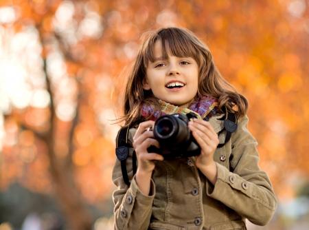 jolie petite fille: photo horizontale, heureux belle petite fille avec photocamera, portrait d'automne