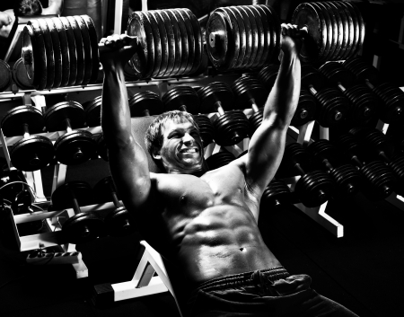 very power athletic guy ,  execute exercise press with  dumbbells, in sport hall,  black-and-white photo