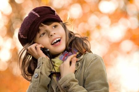 telephony: horizontal photo,  stylish beautiful little girl hold  mobile phone and gladness talk