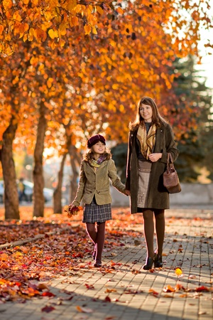 defoliation: Vertical photo,  happy beautiful little girl with mather  walking in park Stock Photo