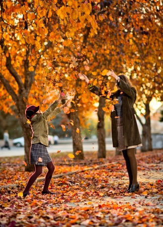 hurl: Vertical photo,  happy beautiful little girl with mather throw up  autumnal leafage, in park