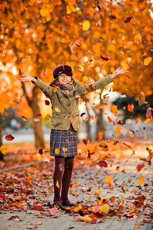 hurl: vertical photo,  happy beautiful little girl joyful  laughter throw up  autumnal leafage, in park