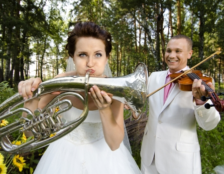 약혼녀: 약혼녀 바이올린, 웨딩 유머 사진에 트럼펫, 신랑 플레이를 불어 스톡 사진