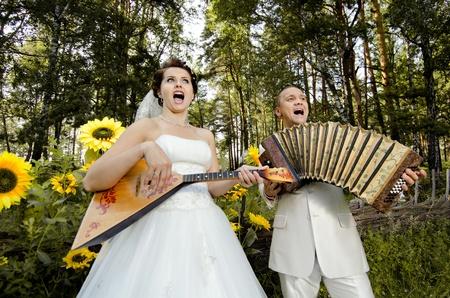 fiancee: fiancee blow the balalaika,  bridegroom play on accordion, wedding  humour photo
