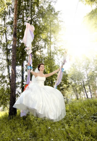 merrymaking: the merry fiancee in white dress on swing, outdoor