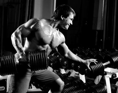 bodybuilding: very power athletic guy ,  execute  traction with  dumbbells, exercise on broadest muscle of back, in sport hall,  black-and-white photo Stock Photo