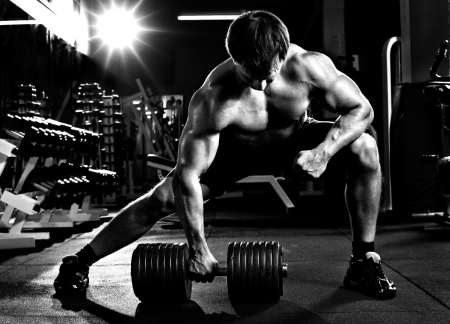 traction: very power athletic guy ,  execute  traction with  dumbbells, exercise on broadest muscle of back, in sport hall,  black-and-white photo Stock Photo