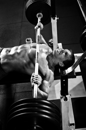 musculation: very power athletic guy ,  execute exercise press with weight, in sport hall, black-and-white photo