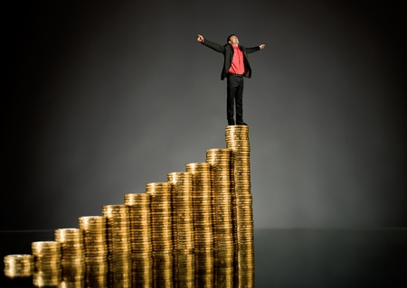 pinnacle: businessman stand on top of  many rouleau gold  monetary  coin, on dark background