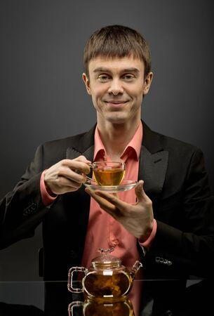 vertical closeup portrait  the  beautiful man hold cup with green  tea,  on brown background photo
