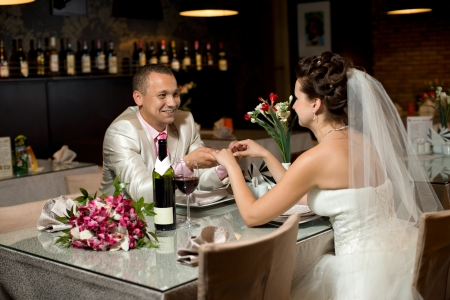 romance image: newly married couple sit at table in restaurant,  romance wedding dinner Stock Photo