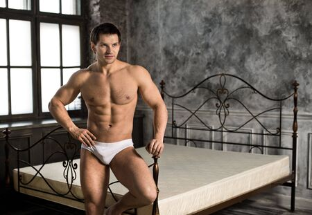 athletic type: the very muscular handsome sexy guy in white briefs ,  in  bedroom Stock Photo