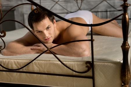 intimo donna: il bel ragazzo sexy in slip bianchi, si trovano nella camera da letto sul letto e sguardo sexy sulla fotocamera