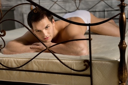 man underwear: the handsome sexy guy in white briefs , lie  in  bedroom on bed and sexy look on camera Stock Photo