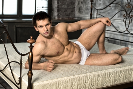 steadfast: the very muscular handsome sexy guy lie on bed  in  bedroom